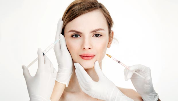 Cosmetologists hands making medical botox injections to beautiful blonde. Skin lifting. Facial treatment. Beauty and spa. Copy space.