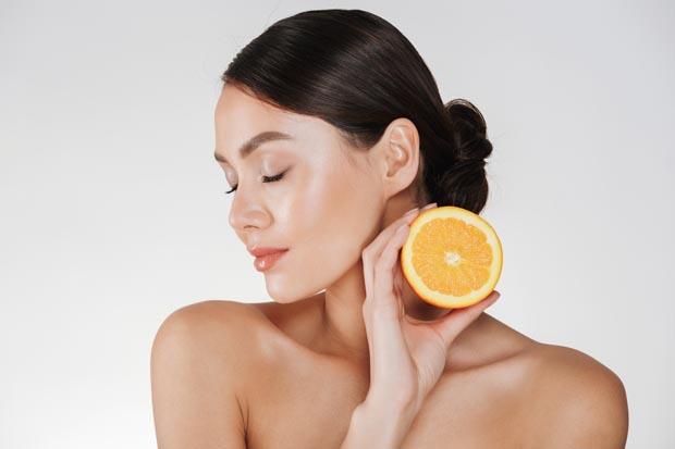 Close up image of charming woman with soft fresh skin holding juicy orange having detox isolated over white background