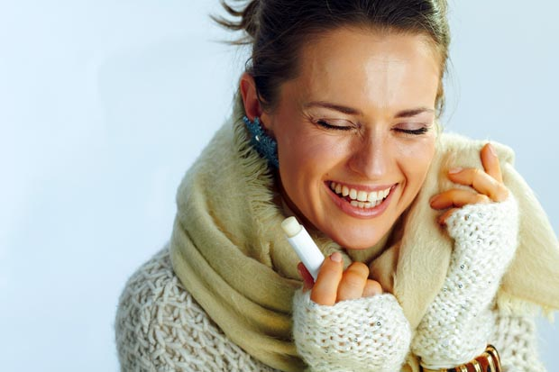 happy stylish middle age woman with lip balm as winter lip care