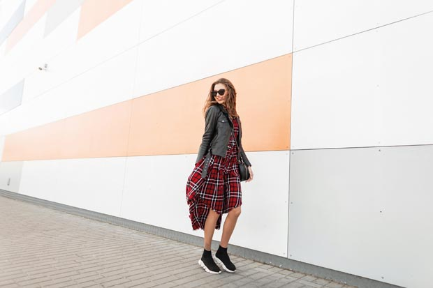 Cool positive young girl in red youth checkered dress in vintage