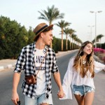 Young beautiful couple on romantic outdoor date enjoys freedom and warm summer evening in south city. Boy in trendy checkered shirt and girl in vintage white blouse walking on the road holding hands.