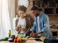Laughing black couple preparing salad in kitchen