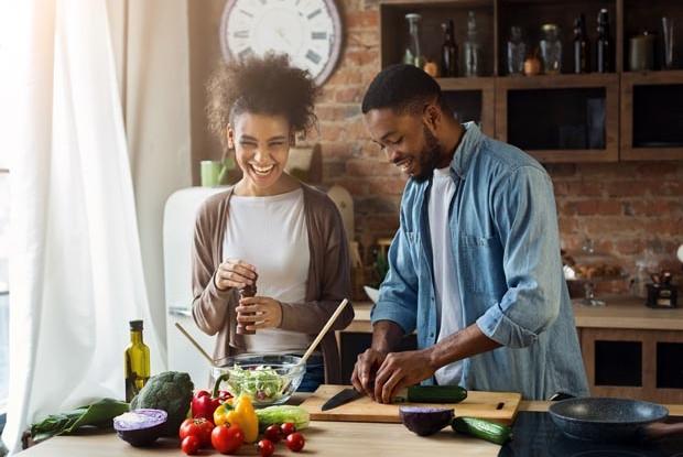 Laughing black couple preparing salad in kitchen