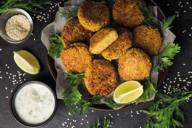 roasted chickpeas falafel patties with garlic yogurt sauce. Top view. black background