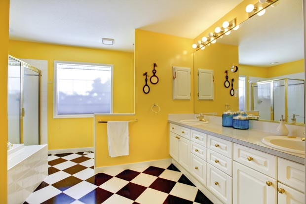 Bright yellow bathroom interior with white cabinets, tile and bi